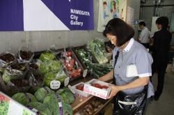 店内で野菜を手に取る来店者