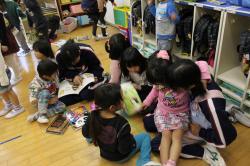 保育園児に本を読んであげる中学生