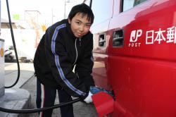 車に給油をする中学生