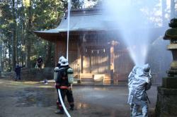 神社拝殿に向けての放水作業