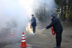 消火器を使って初期消火に当たる神社総代の方々