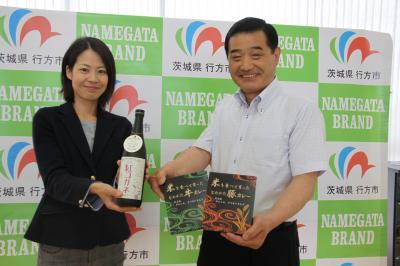 6月27日から発売されるサツマイモ焼酎と一緒に市長が商品を説明